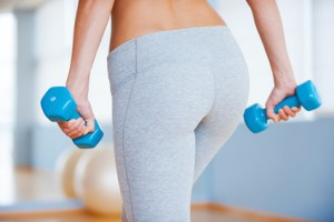 Perfect buttocks. Rear view of sporty woman with perfect buttocks holding dumbbells while standing in health club